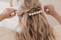 04 a half updo with twists and loose waves and accented with a large pearl hair barrette