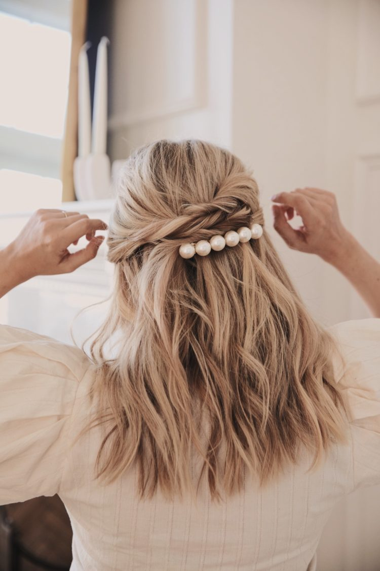 a half updo with twists and loose waves and accented with a large pearl hair barrette