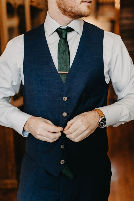 a navy blue suit with a waistcoat, a green snake print tie for a groom's or groomsman's look