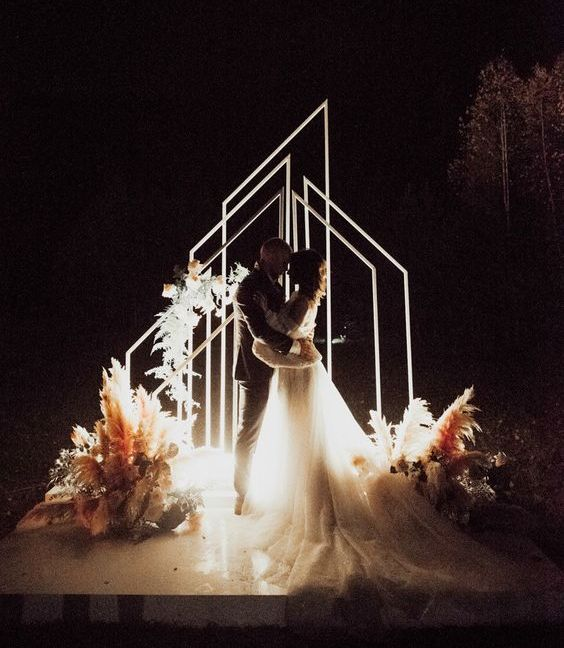 geometric LED arches and lights on the ground plus florals and pampas grass for a gorgeous night wedding ceremony