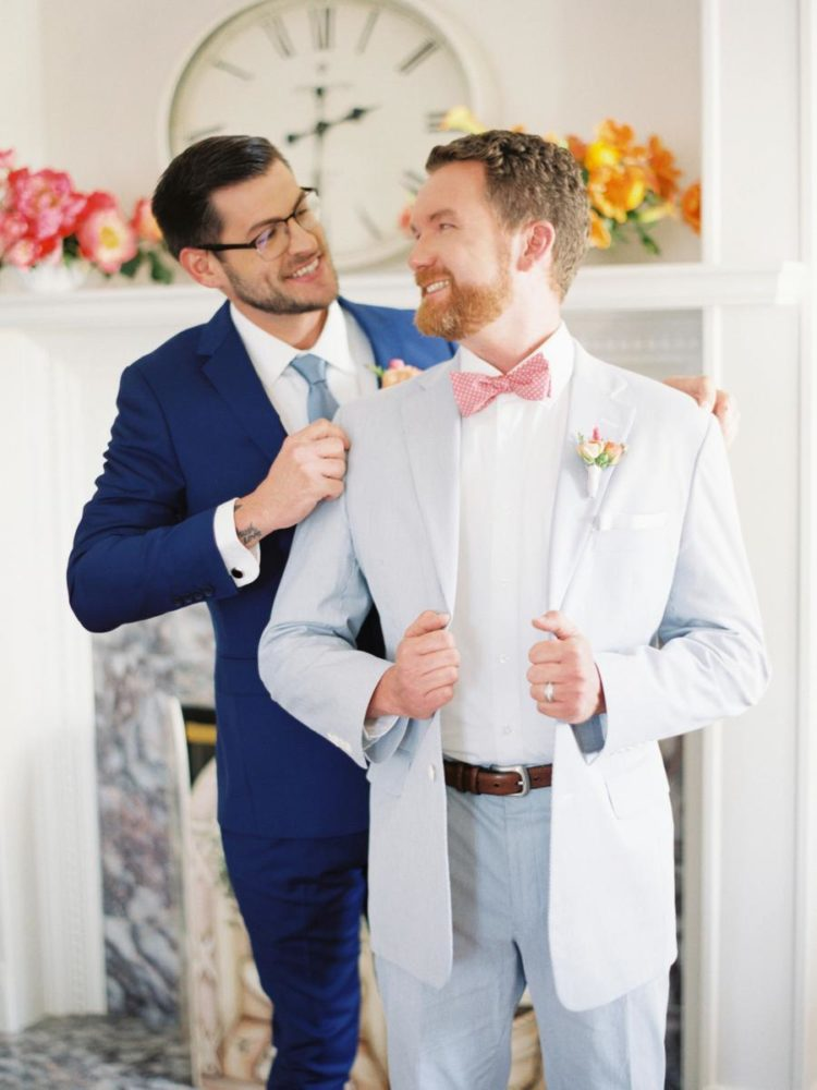 One groom was wearing a light blue suit with a coral bow tie and the other groom was wearign a bold blue suit with a light blue tie