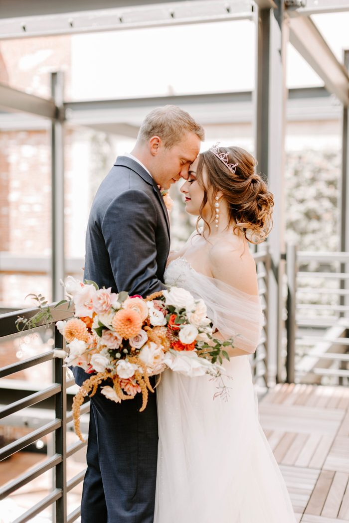 The wedding bouquet was done with orange, red and blush blooms and much texture and dimension