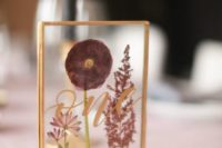 05 a chic gold framed table number with mauve and pink pressed blooms and elegant calligraphy for a fall wedding