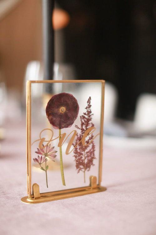 a chic gold framed table number with mauve and pink pressed blooms and elegant calligraphy for a fall wedding