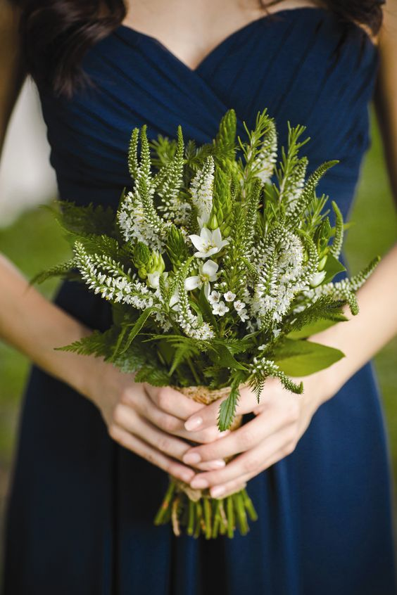 a navy strapless bridesmaid dress and a greenery and white bloom bouquet for a navy and green wedding