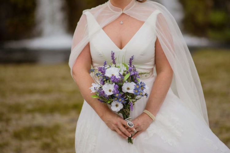 The bride was wearing an A-line wedding dress with a deep neckline and a sheer cape plus some chic accessories