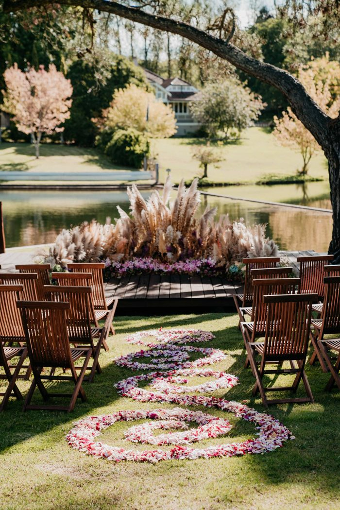The ceremony space was done with pampas grass, pink blooms, greenery and with pink petals