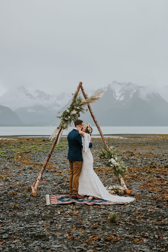 The ceremony took part outdoors, with a wooden arch with greenery and grass and it was pouring with rain