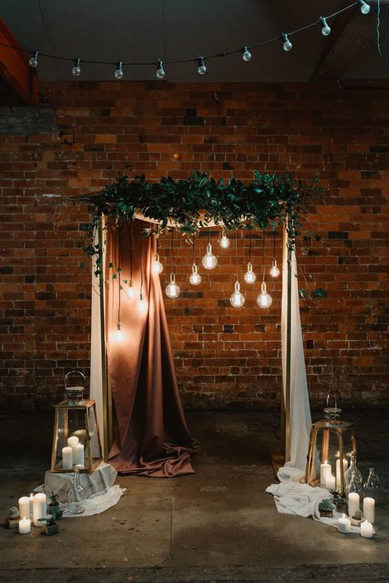 a chic wedding arch with a copper curtain, bulbs hanging down, greenery, candle lanterns and cacti in pots