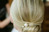 06 a low and tight bun with a sleek top and large pearl pins is a gorgeous and fresh idea for a modern or minimalist bride