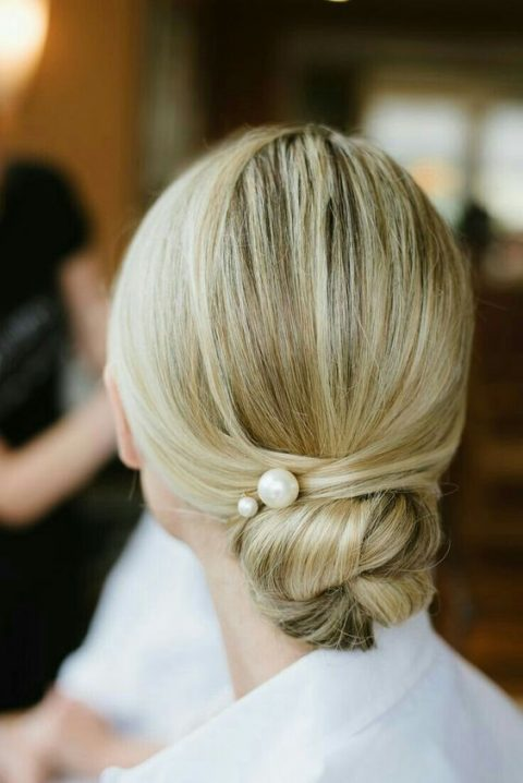 a low and tight bun with a sleek top and large pearl pins is a gorgeous and fresh idea for a modern or minimalist bride
