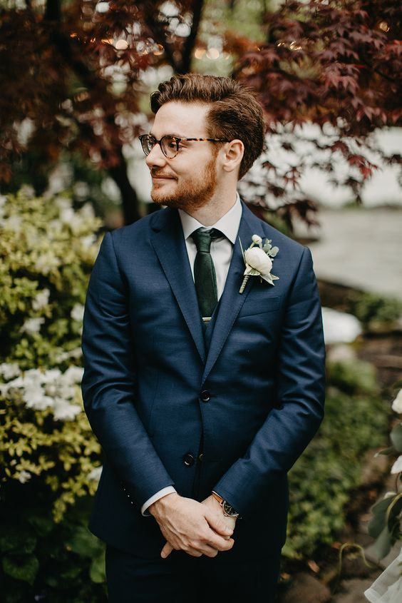 a navy three-piece suit, a dark green tie and a neutral floral boutonniere to refresh the whole look
