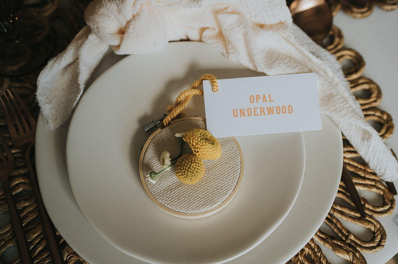 Little embroidery hoops with billy balls and rope plus a card is a cool idea to mark the place setting