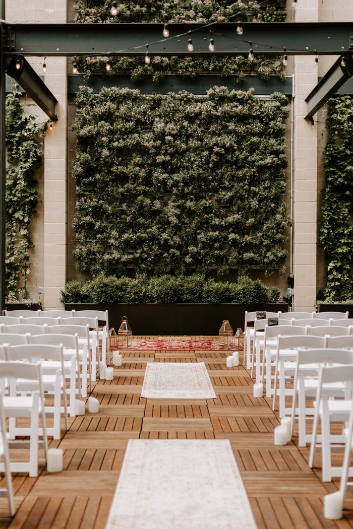 The ceremony space was done with candles, a greenery wall and simple white chairs