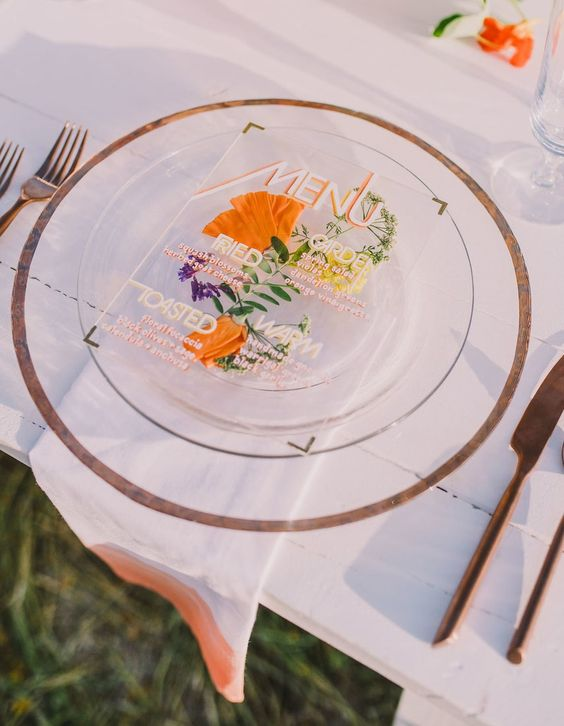 a colorful wedding menu with bright pressed flowers and greenery plus elegant gold corners for a summer menu