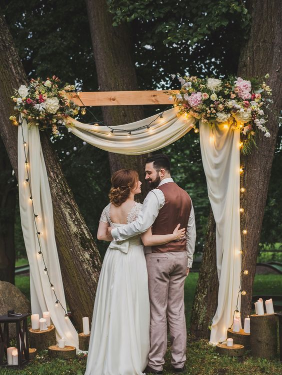 a cozy rustic wedding arch with string lights, neutral fabric, lush florals and candles on tree slices around
