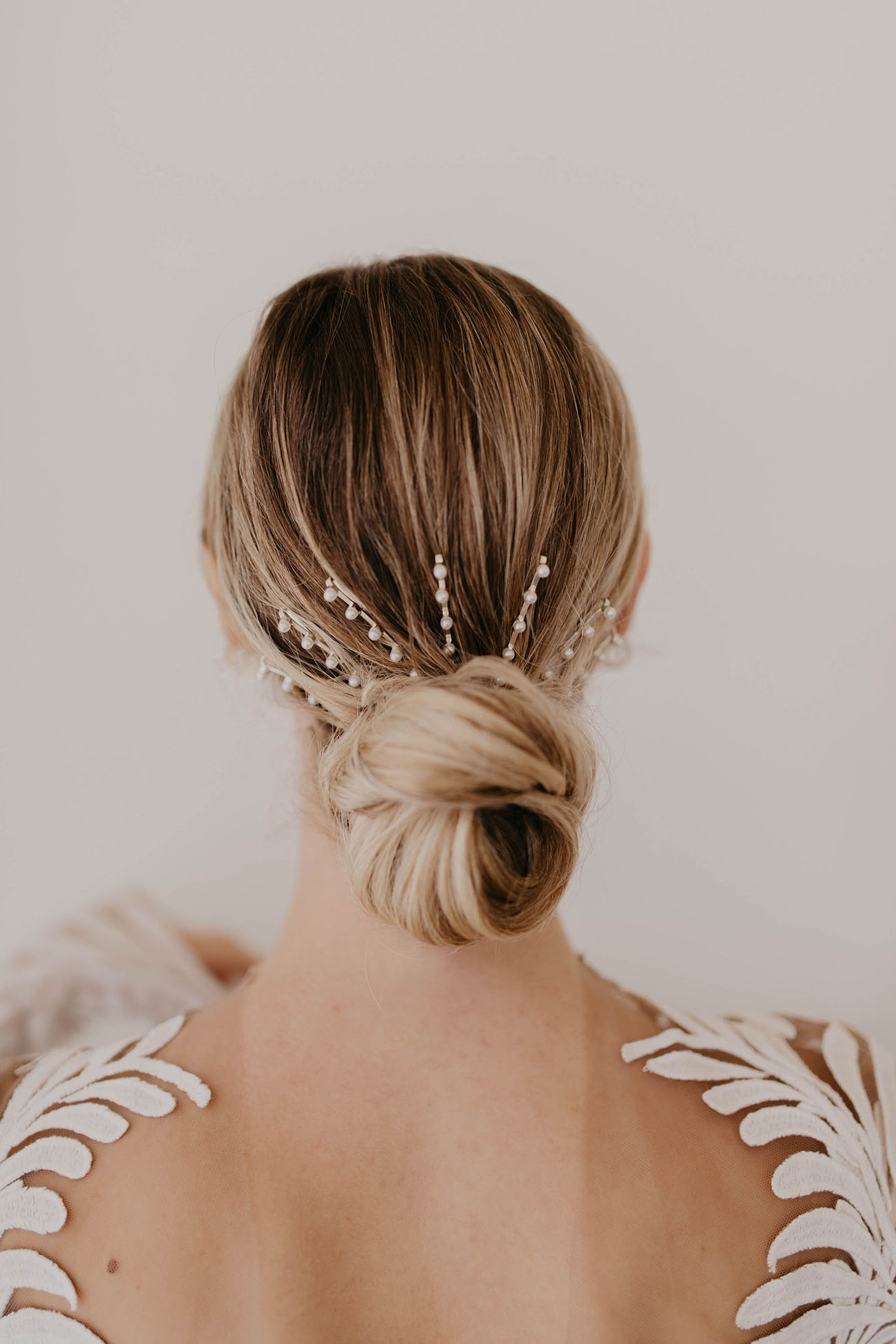 a low bun accented with a large hair barrette with pearls looks modern, feminine and very chic