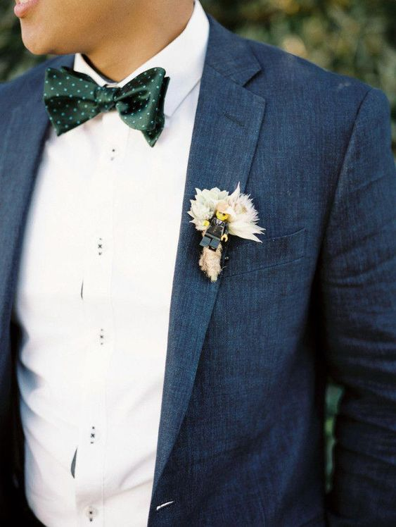 a stylish groom's blue suit with a white shirt, a green polka dot bow tie and a neutral boutonniere