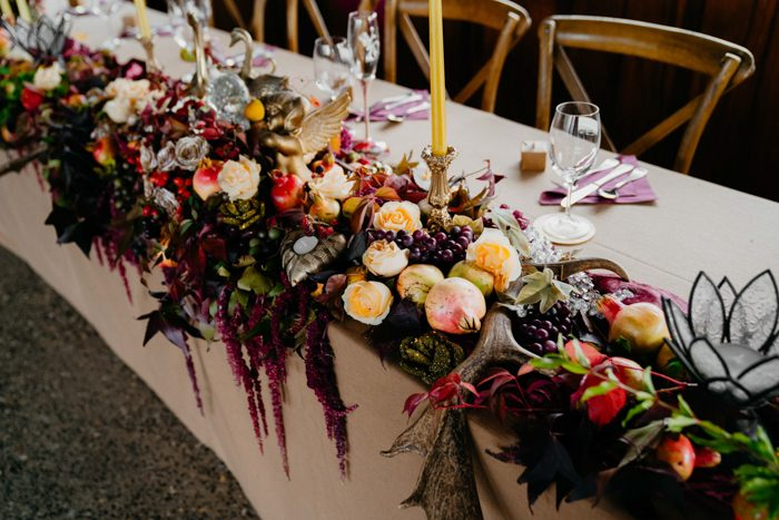 Lush abundant table runners with cascading blooms, greenery, antlers and fruits and candles were amazing