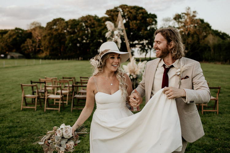 The bride changed for a plain A-line wedding dress with spaghetti straps and a white hat, and the groom put on a blazer
