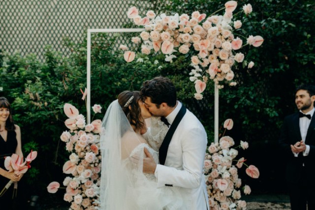 The wedding arch was decorated with super lush blush blooms for a romantic feel