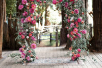 08 The wedding arch was done with lush greenery and bold blooms in fuchsia and pink plus deep reds