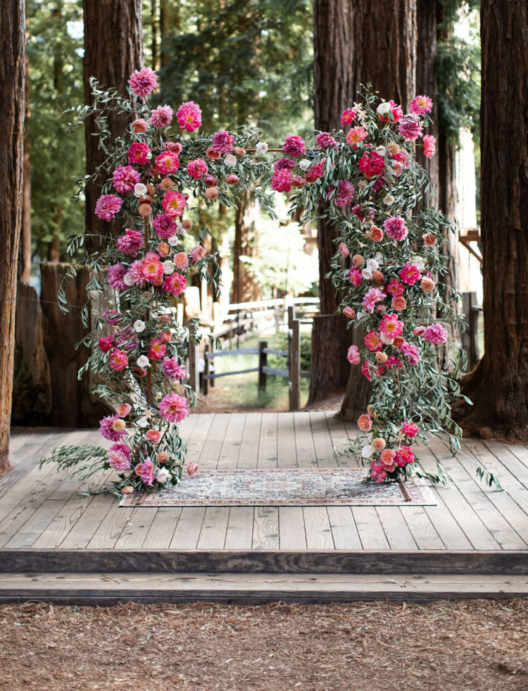 The wedding arch was done with lush greenery and bold blooms in fuchsia and pink plus deep reds