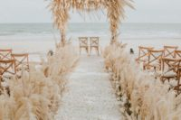 08 The wedding ceremony space was done with pampas grass and white blooms and petals