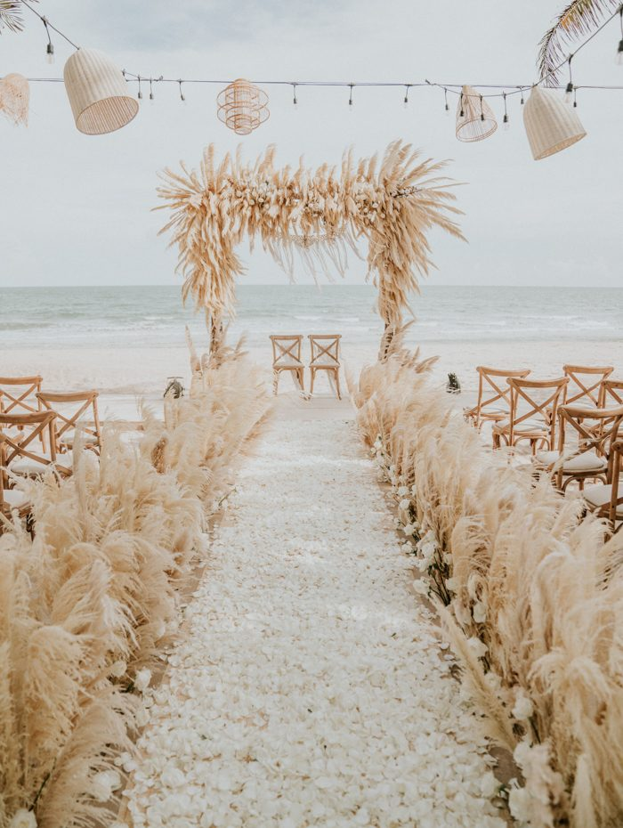The wedding ceremony space was done with pampas grass and white blooms and petals