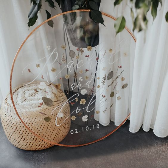 a cute round wedding sign with pressed flowers and greenery plus a wedding date is ideal for a boho wedding
