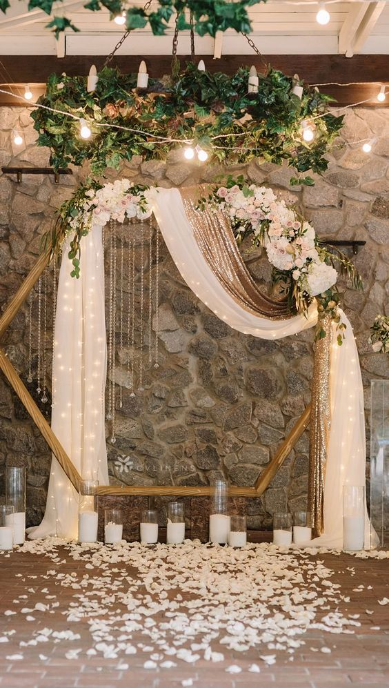 a glam hexagon wedding arch decorated with lush pastel and neutrla blooms, greenery, candles and a white and gold curtain with lights inside plus petals around
