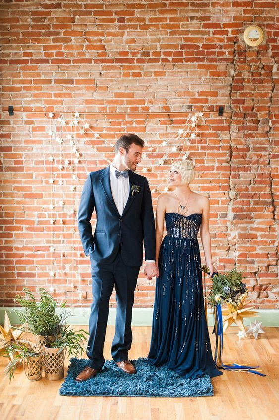 the couple wearing navy and greenery and gold wedding decor around themto match the color scheme