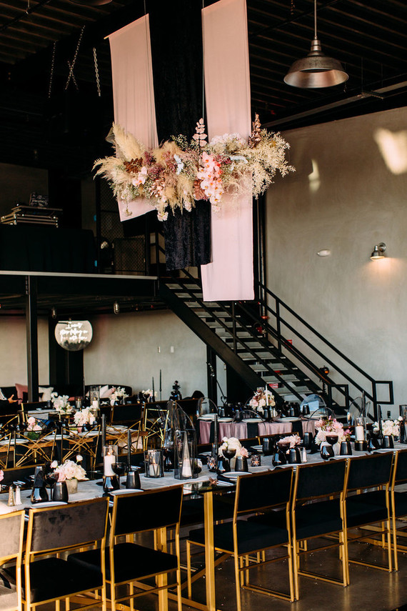 A flowing overhead floral decoration with pampas grass is a very chic addition to the venue decor