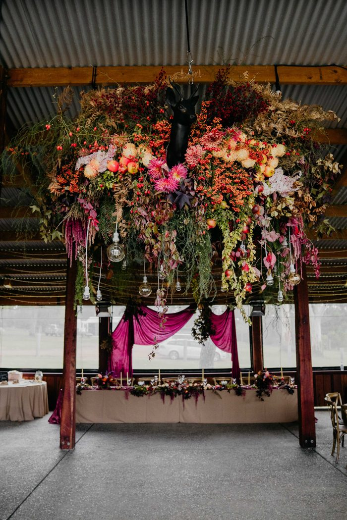 Look at this gorgeous floral explosion in deep red, pink, with cascading greenery, bulbs and lights