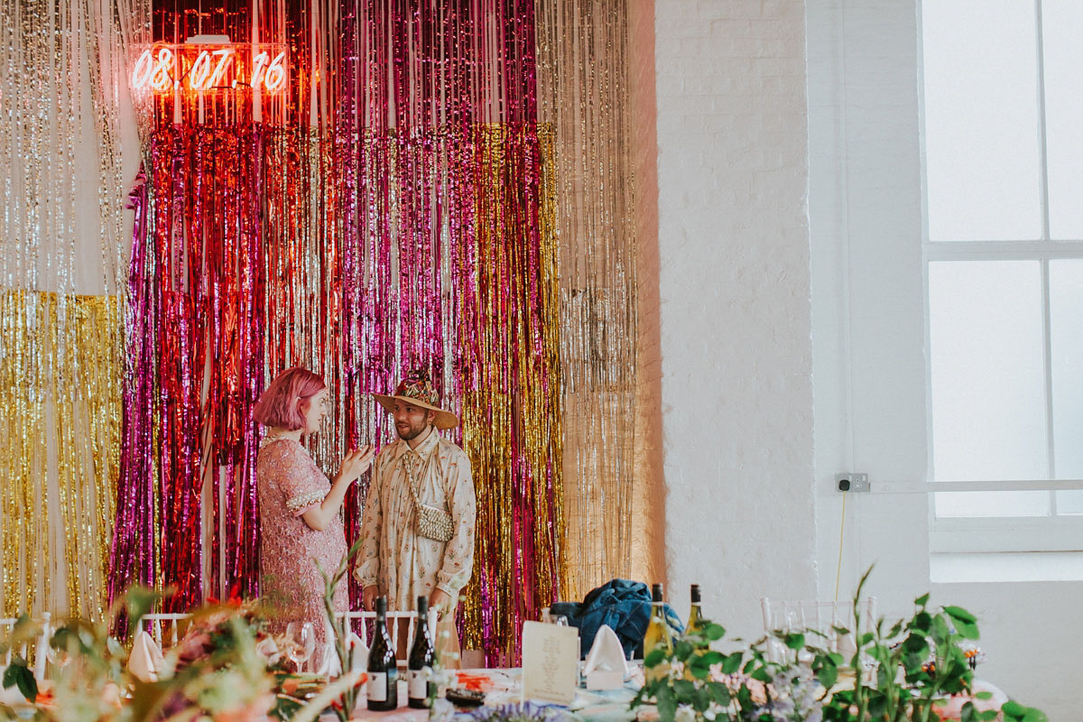 The wedding backdrop was super shiny in gold, copper and hot pink with a neon sign