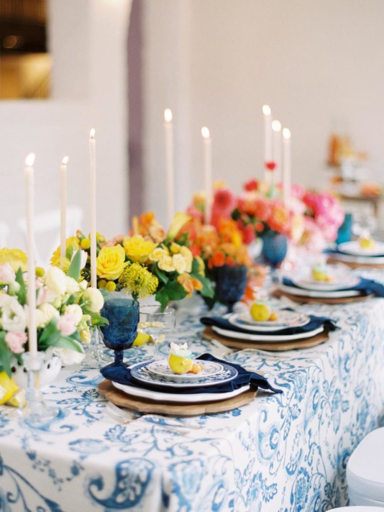 The wedding reception space was done with bright ombre blooms, navy touches and printed plates and tablecloths plus tall candles
