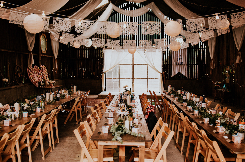 The wedding reception space was done with doilies, paper lanterns, eucalyptus table runners, candles and simple and neutral blooms