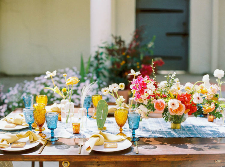 The wedding tablescape was done with a blue table runner, colored glasses, bright florals and cacti