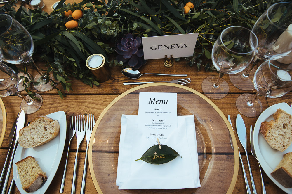 The wedding tablescape was uncovered, with a lush greenery, fruit and succulent runner and some candles in metallic canldeholders