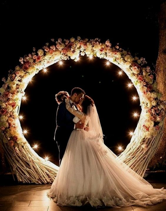a glam wedding arch fully covered with white and pink blooms and with lights to highlight your couple as much as possible