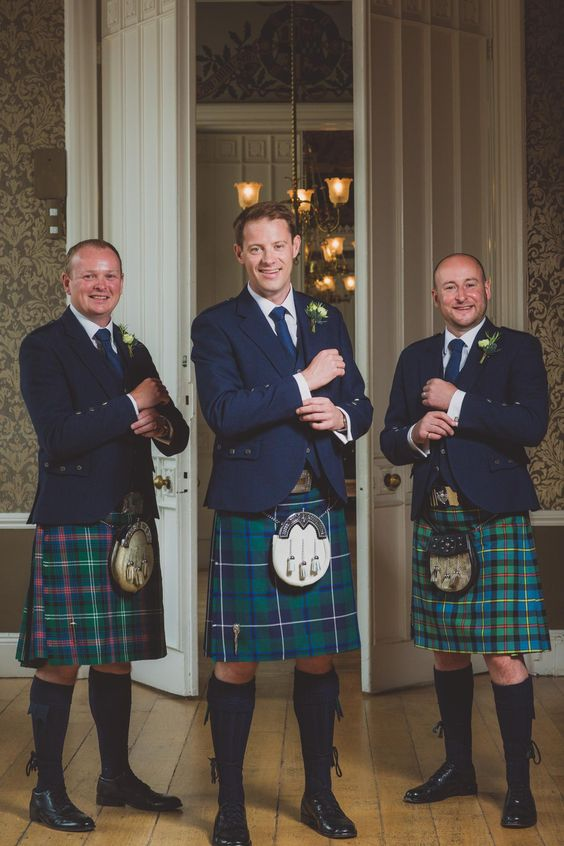 the groom and groomsmen wearing navy blazers and ties and plaid kilts plus traditional shoes and socks