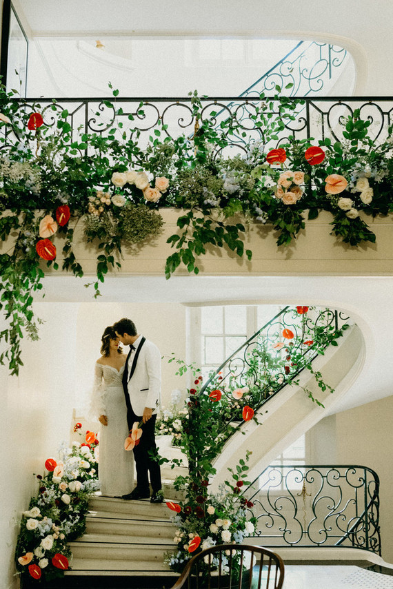 The staircase was done with lush greeneyr, white, blush and red blooms