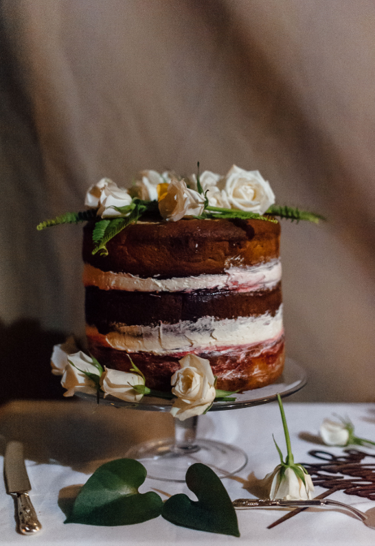 The wedding cake was naked, with some greenery and fresh blooms on top