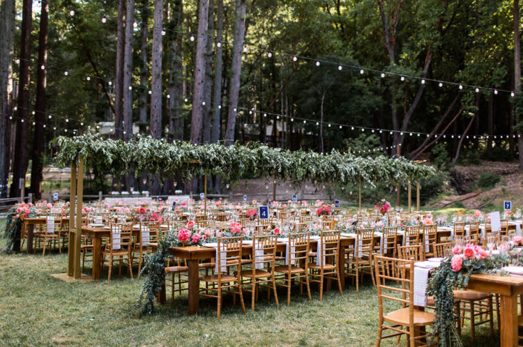 The wedding reception took place outdoors, with lights and greenery over the tables