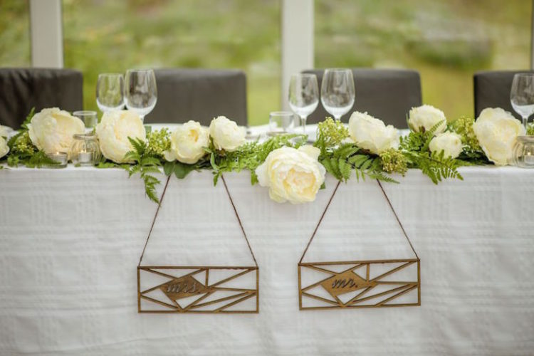 The wedding table decor was done with simple wooden signs, greenery and white blooms