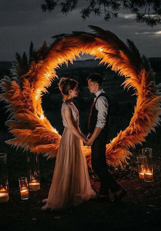 a lush pampas grass round arch with lights in it and candles all around is a super trendy option to try