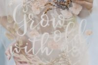 10 a round acrylic wedding sign with pressed dried blooms and white calligraphy and looks very tender and chic