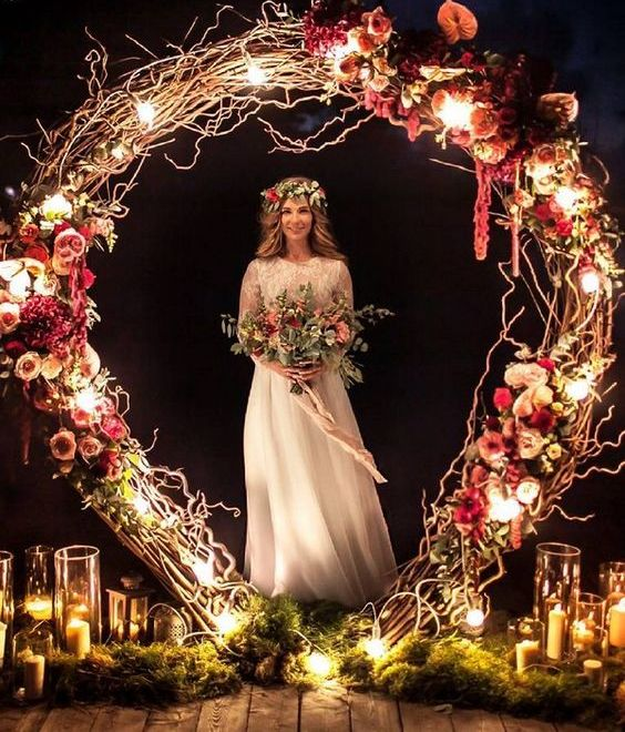 a lush wedding arch decorated with twigs, lush blush and burgundy blooms and lights plus candles around the arch