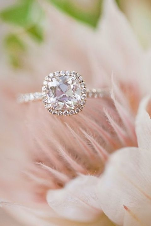 a rose gold engagement ring with a cushion pink diamond and a halo for a romantic person