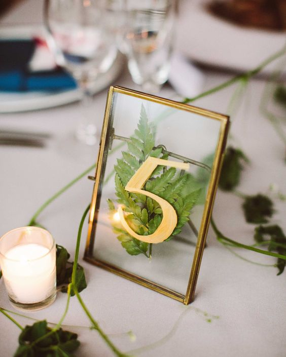 a stylish fern table number with gold and in a gold frame will be a nice and chic addition to your table